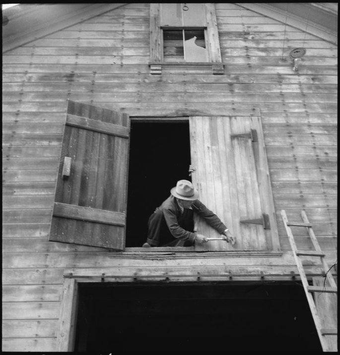 Centerville, California. Nailing the hayloft door on the morning of evacuation. Farmers and other evacuees of Japanese ancestry will be given opportunities to follow their callings at War Relocation Authority centers where they will spend the duration.